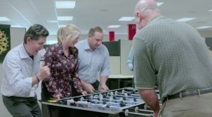 large image of people playing foosball at work